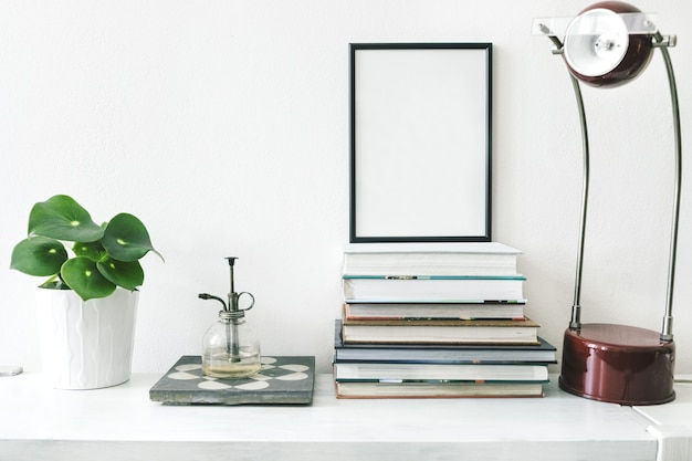 Stilvolle komposition aus kreativem wohnzimmerinterieur mit schwarzem posterrahmen, pflanzen in hipster-designtöpfen, büchern, lampen und accessoires auf dem weißen regal. minimalistisches konzept.