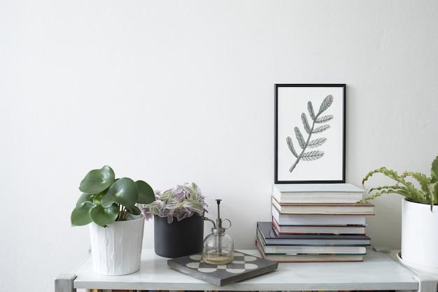 Stilvolle komposition aus kreativem wohnzimmerinterieur mit schwarzem posterrahmen, pflanzen in hipster-designtöpfen und accessoires auf der weißen kommode. minimalistisches konzept.