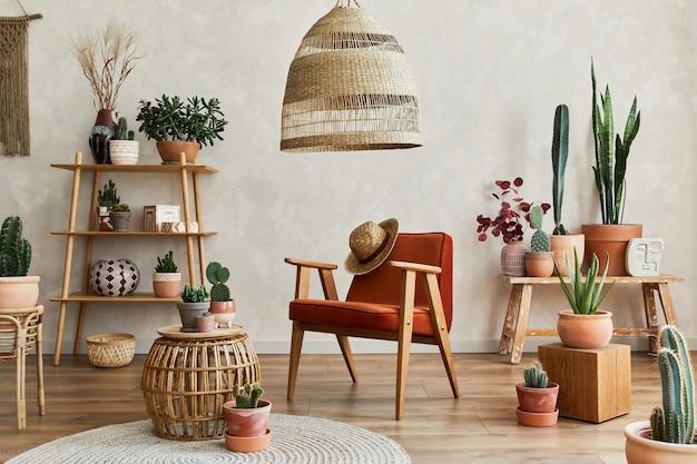 Stilvolle komposition aus modernem wohnzimmer mit kopienraum, vielen kakteen und pflanzen, sessel, holzregalen und rattanzubehör. kreative wand, teppich auf dem boden. vorlage.