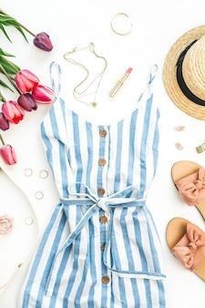Stilvolle komposition der weiblichen mode des sommers. kleid, hausschuhe, stroh, tulpenblumen und accessoires auf weißem hintergrund. flach legen
