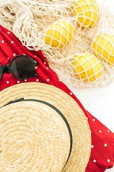 Stilvolle komposition der weiblichen mode des sommers. rotes kleid, stroh, schnurbeutel, sonnenbrille und zitronen auf weißem hintergrund. flach legen