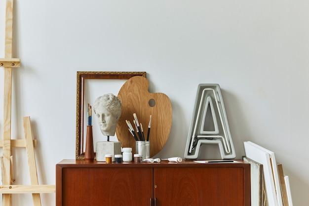 Stilvolle komposition des künstlerarbeitsbereichs mit design retro teak kommode, rahmen, staffelei, buch, dekoration und malzubehör.