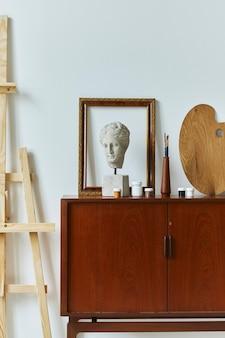 Stilvolle komposition des künstlerarbeitsraums mit design-retro-teakkommode, posterrahmen, buch, dekoration und malzubehör. vorlage.