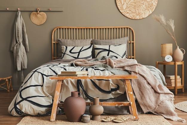 Stilvolle komposition des schlafzimmer-interieurs mit holzbett, möbeln, getrockneten blumen in der vase, rattan-dekoration, vasen und eleganten accessoires. schöne bettwäsche, decke und kissen. gemütliche wohnkultur.