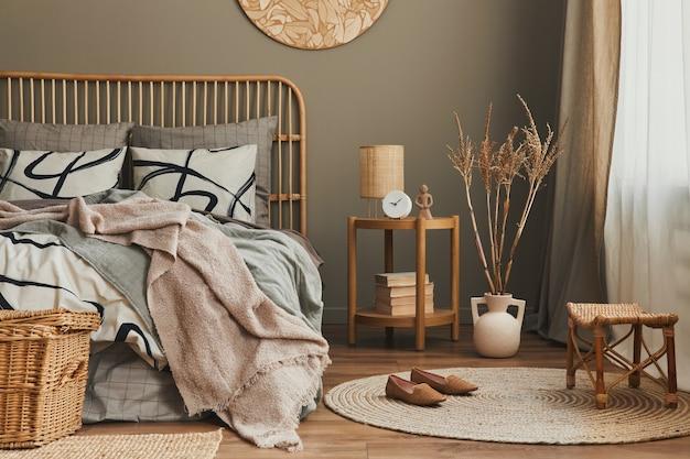 Stilvolle komposition des schlafzimmer-interieurs mit holzbett, möbeln, teppichdekor, hocker, rattan-dekoration, vasen und eleganten accessoires. schöne bettwäsche, decke und kissen. gemütliche wohnkultur.
