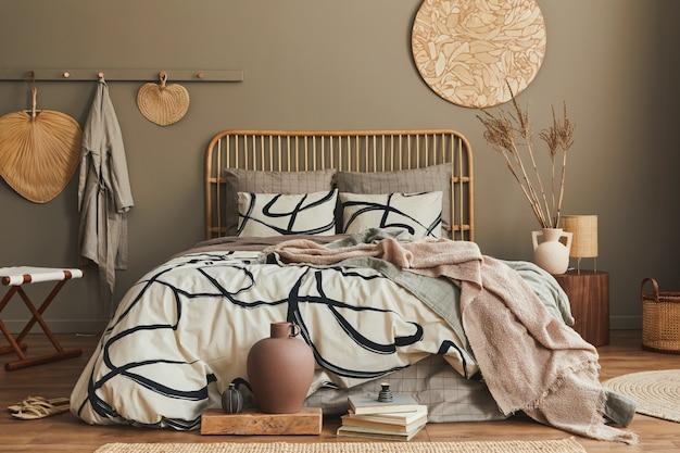 Stilvolle komposition des schlafzimmerinterieurs mit holzbett, möbeln, getrockneten blumen in der vase, rattan-dekoration und eleganten accessoires. schöne bettwäsche, decke und kissen. gemütliche wohnkultur.