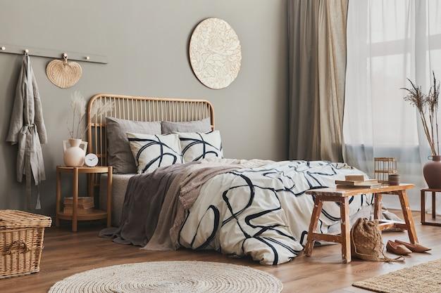 Stilvolle komposition des schlafzimmerinterieurs mit holzbett, möbeln, getrockneten blumen in vase, rattandekoration, vasen und eleganten accessoires