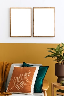 Stilvolle komposition des wohnzimmerinterieurs mit design-sofa, zwei rahmen, pflanzen, kissen und persönlichen accessoires in honiggelber wohnkultur.