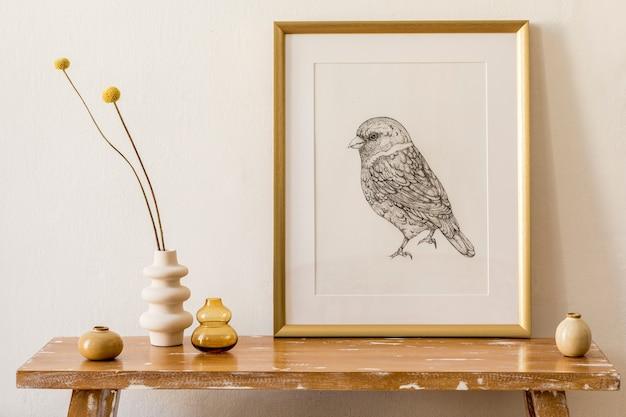 Stilvolle komposition des wohnzimmerinterieurs mit goldrahmen, holzbank, getrockneter blume in vase, weißer dekorationswand und eleganten persönlichen accessoires in moderner wohnkultur.
