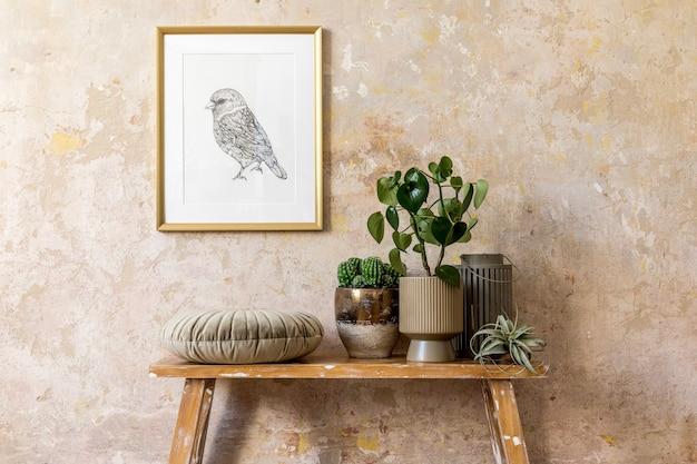 Stilvolle komposition des wohnzimmerinterieurs mit goldrahmen, holzbank, kissen, pflanzen, luftpflanze, laterne, grunge-wand und eleganten persönlichen accessoires in moderner wohnkultur.