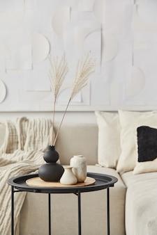 Stilvolle komposition im ausgefallenen interieur mit holzcouchtisch, getrockneten blumen in vase, kissen, decke, kunstmalerei und buch in moderner wohnkultur. einzelheiten. vorlage.