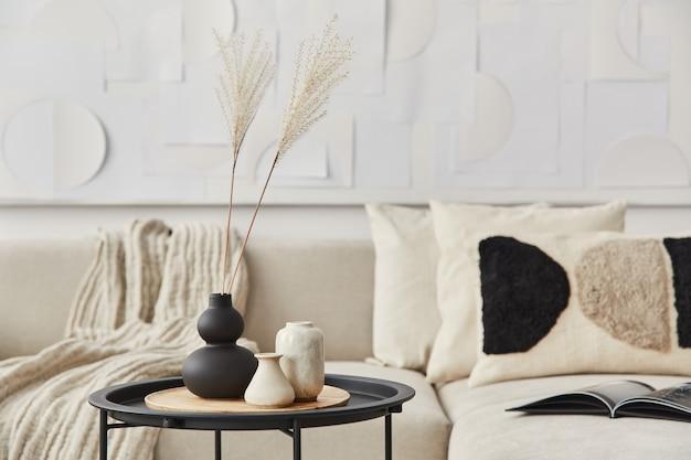 Stilvolle komposition im ausgefallenen interieur mit holzcouchtisch, getrockneten blumen in vase, kissen, decke, kunstmalerei und buch in moderner wohnkultur. einzelheiten..