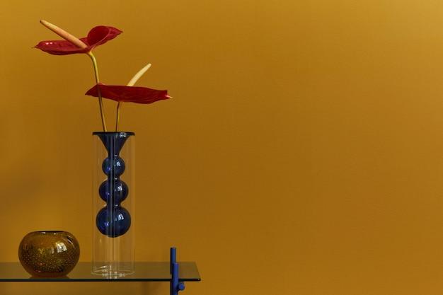 Stilvolle komposition im modernen wohnzimmer mit design-couchtisch, tasse, buch und roter blume. nahansicht. gelbe wand..