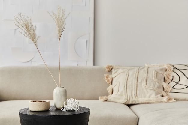 Stilvolle komposition im schicken interieur mit schwarzem holztisch, getrockneten blumen in vase, kissen, decke in moderner wohnkultur. einzelheiten. vorlage.