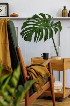 Stilvolle komposition im wohnzimmer mit design-sessel, plaid, pflanze, tasse kaffee, blume in vase, buch, holzpaneelen mit regal und eleganten accessoires in moderner wohnkultur.