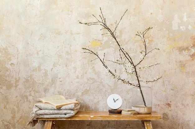 Stilvolle komposition im wohnzimmer mit designuhr, holzbank, getrockneten blumen in vase, grunge-wand und eleganten persönlichen accessoires in moderner wohnkultur. platz kopieren.