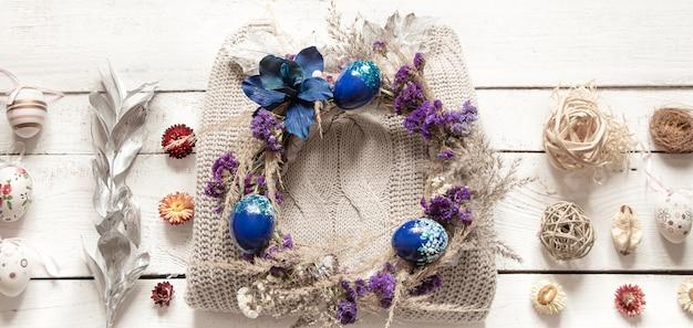 Stilvolle komposition mit einem osterkranz und eiern im trendblau.
