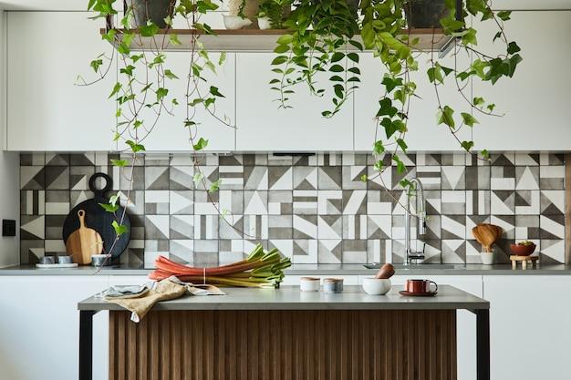 Stilvolle kücheneinrichtung mit essbereich. arbeitsbereich mit küchenzubehör im hintergrund. kreative wände mit holzpaneelen. minimalistischer stil ein pflanzenliebeskonzept.