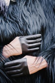 Stilvolle kurze handschuhe auf einem mädchen in einem schwarzen pelzmantel