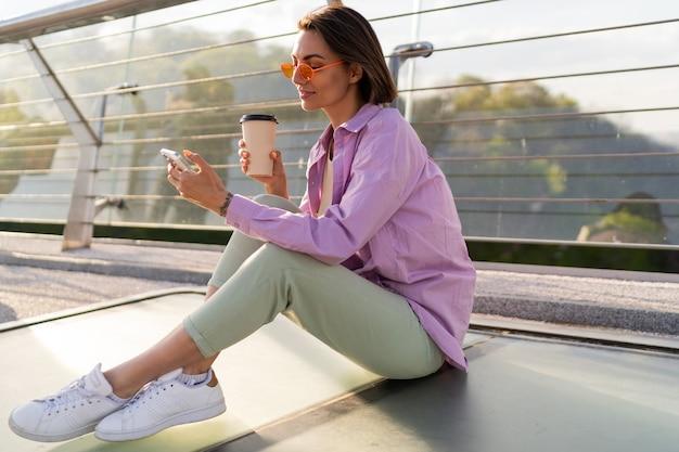 Stilvolle kurzhaarige frau, die auf moderner brücke sitzt, kaffee genießt und handy benutzt