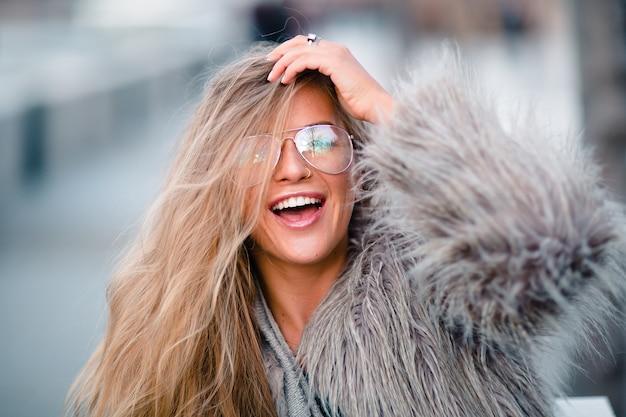 Stilvolle lachende jugendlich frau im pelz-öko-mantel