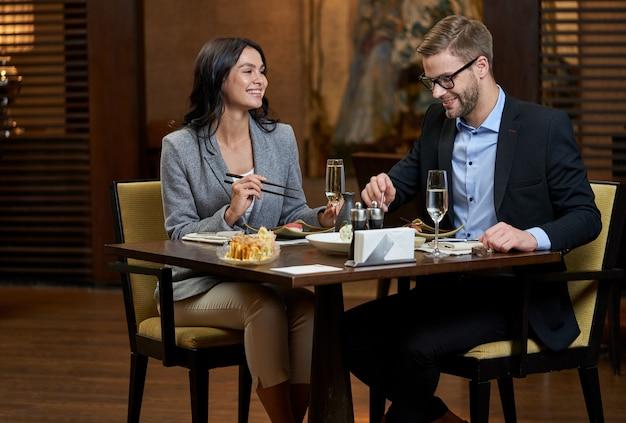 Stilvolle lächelnde dame, die essstäbchen hält und männer in gläsern beobachtet, die sushi mit seiner gabel am esstisch im restaurant stechen?