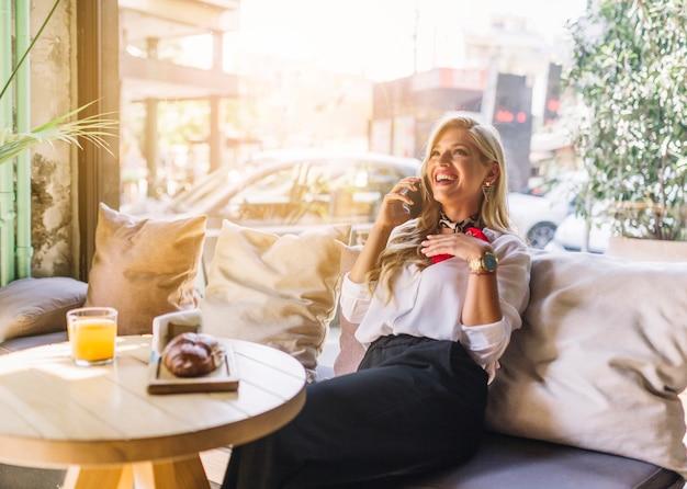 Stilvolle lächelnde junge frau, die über dem sofa spricht am handy im restaurant sitzt