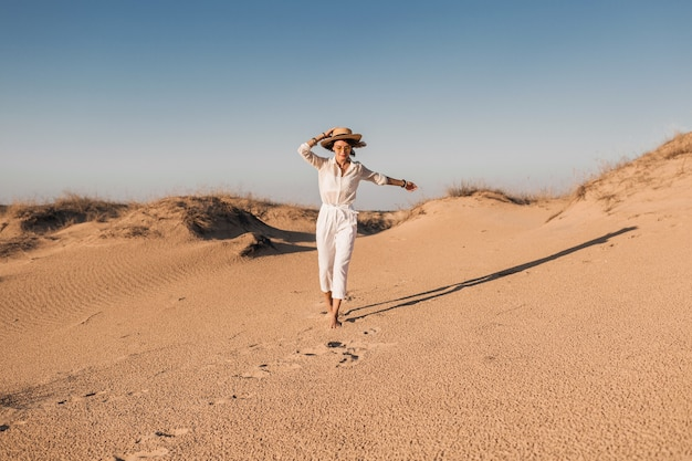 Stilvolle lächelnde schöne frau, die im wüstensand im weißen outfit läuft, das strohhut auf sonnenuntergang trägt