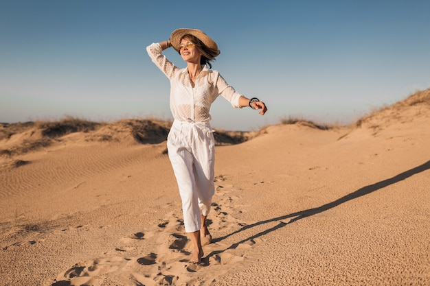 Stilvolle lächelnde schöne glückliche frau läuft und springt in wüstensand im weißen outfit, das strohhut auf sonnenuntergang trägt