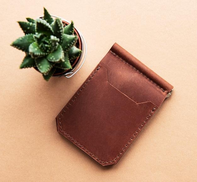 Stilvolle lederbrieftasche und kaktuspflanze