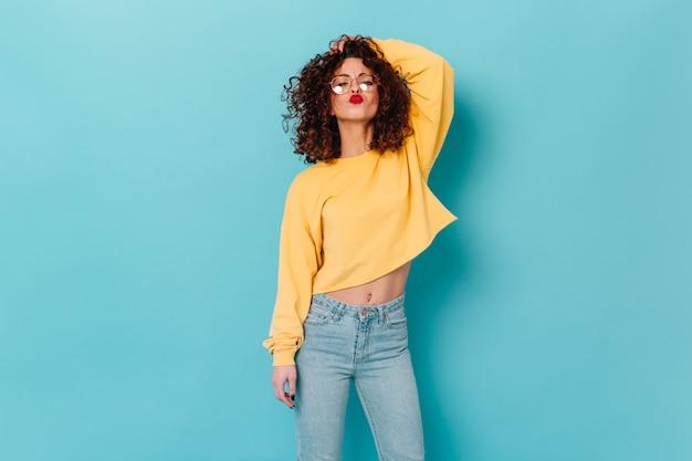 Stilvolle lockige frau mit rotem lippenstift berührt haare und bläst kuss. porträt des mädchens in den gläsern und im gelben pullover auf blauem raum.