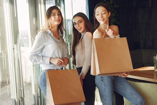 Stilvolle mädchen, die in einem café mit einkaufstüten stehen