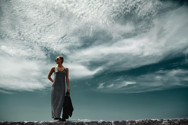 Stilvolle mädchenfrau in lässiger hipster-kleidung, die hinter himmel mit wolken aufwirft
