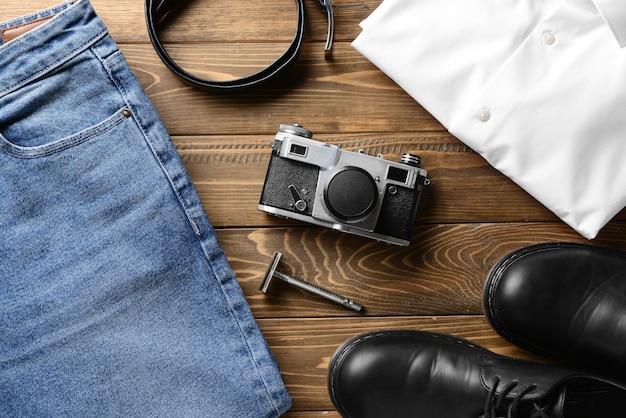 Stilvolle männliche kleidung mit zubehör und fotokamera auf holztisch