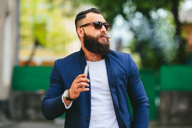Stilvolle mann mit sonnenbrille und elektronische zigarre