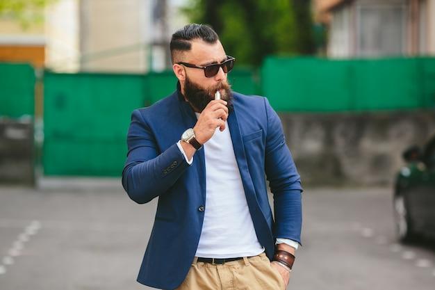 Stilvolle mann posiert während eine elektronische zigarre rauchen