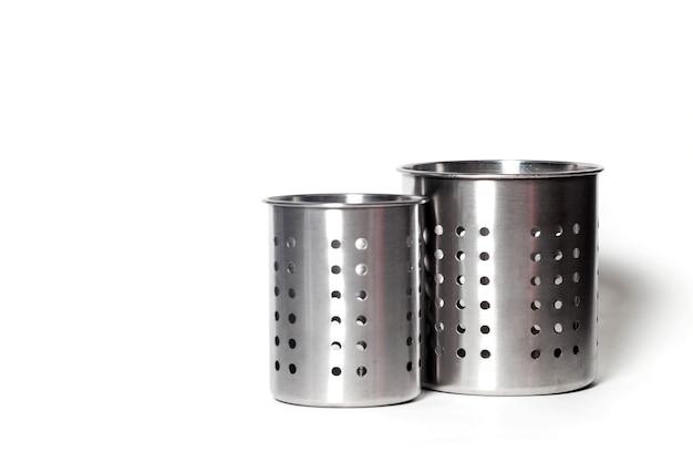 Stilvolle metallbehälter aus edelstahl zum aufbewahren von küchenutensilien auf weißem, isoliertem hintergrund. verpackungsbehälter für gabeln, löffel, messer. konzept des küchenzubehörs für die website. platz kopieren