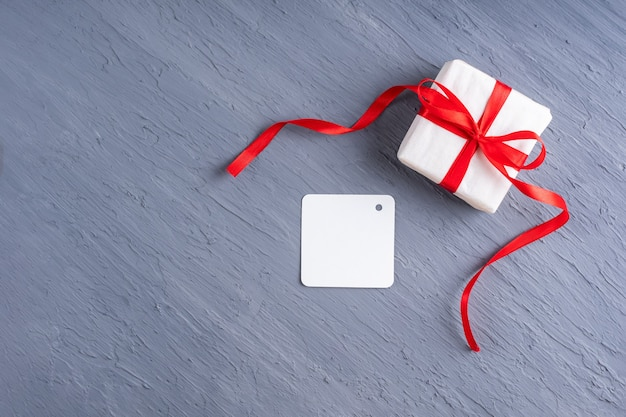 Stilvolle minimalistische postkarte mit platz für text. geschenk in weißem papier mit einem roten band, postkarte auf einem grauen hintergrund