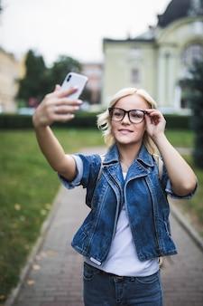 Stilvolle mode blondes mädchen frau in jeans suite und brille macht selfie auf ihrem handy in der stadt am morgen