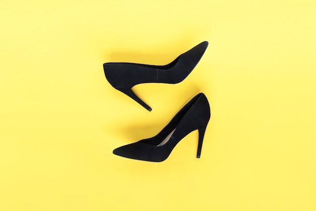 Stilvolle mode schwarze schuhe high heels auf gelbem hintergrund flache ansicht von oben trendiger hintergrund modeblog-look