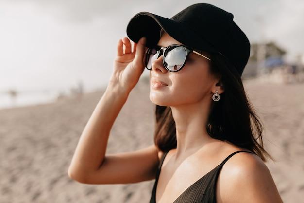 Stilvolle moderne frau im trendoutfit, die auf dem ozean mit glücklichem lächeln sieht, das kappe und brille trägt und heiße heiße sommertage junges kaukasisches weibliches modell am seeufer genießt