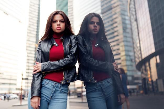 Stilvolle moderne frau mit geglättetem haar in einem modischen roten pullover, schwarzer lederjacke und blauen jeans, die auf der straße posieren