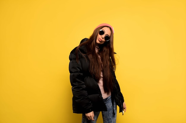 Stilvolle modische frau, die schwarze jacke und sonnenbrille und rosa mützenaufstellung trägt