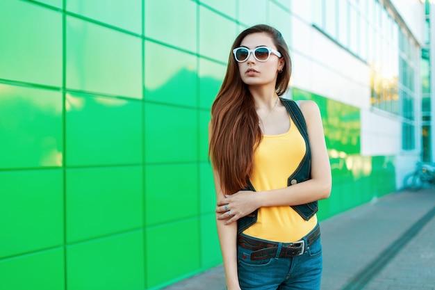 Stilvolle modische frau in der sonnenbrille, die nahe einem grünen gebäude steht.