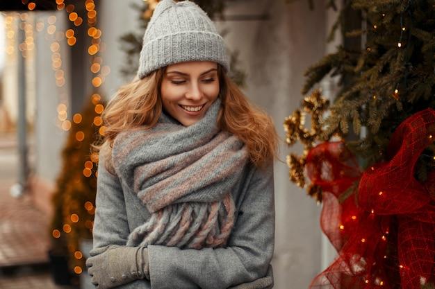 Stilvolle modische junge frau mit einem glücklichen lächeln in gestrickter kleidung mit grauer mütze und modeschal auf der straße in den winterferien nahe den lichtern