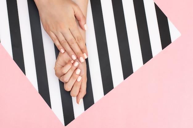 Stilvolle modische weibliche maniküre. hände der jungen frau auf rosa