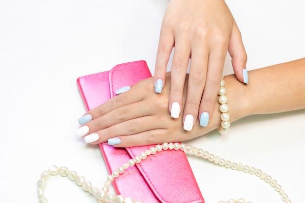 Stilvolle modische weibliche maniküre. schöne hände einer jungen frau auf einem hintergrund von blumen und perlen von perlen