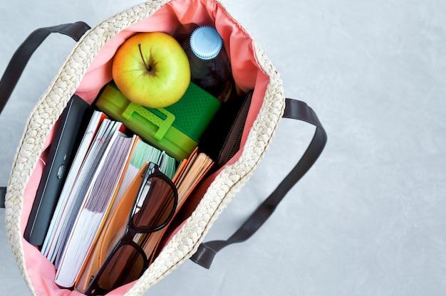 Stilvolle modische wicker-tasche mit lehrbüchern und notizbüchern