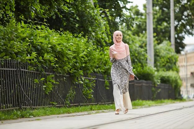 Stilvolle muslimische frau, die über straße geht
