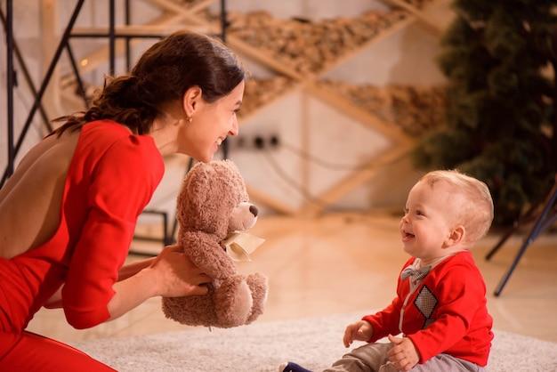 Stilvolle mutter, die mit baby im raum spielt